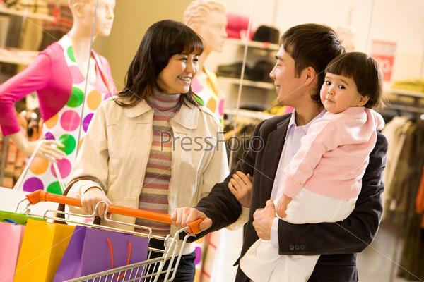 Дружная семья на фоне витрины совершает покупки в супермаркете