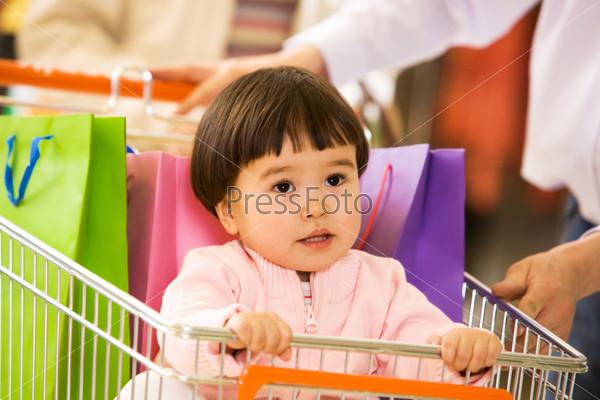 Хорошенькая девочка сидит в тележке для покупок и выглядывает из нее
