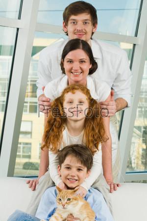 Фотография на тему Радостные дети с родителями и кошкой стоят друг над другом на фоне окна
