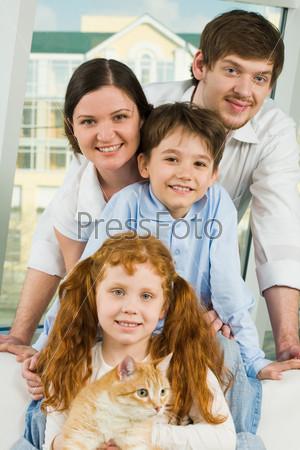 Счастливая семья с рыжим котом смотрит в камеру и улыбается