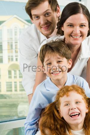 Счастливые лица членов семьи, которые смотрят в камеру и смеются