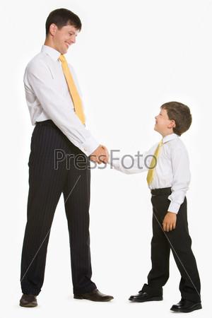 Отец и сын в галстуках приветствуют друг друга рукопожатием на белом фоне