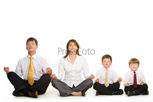 Семья из четырех человек сидит в позе лотоса в ряд
