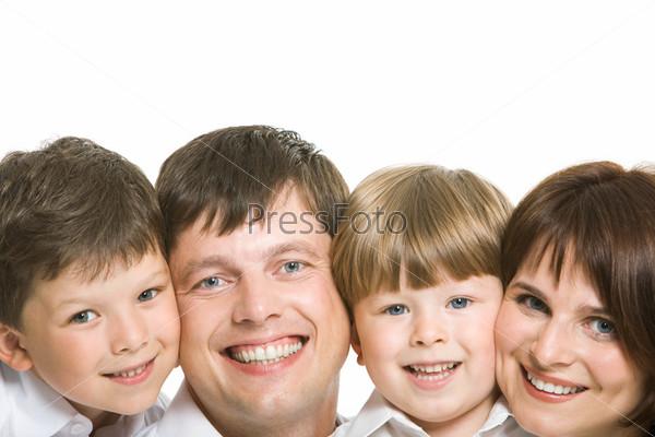 Улыбающиеся лица семьи смотрят близко в камеру на белом фоне