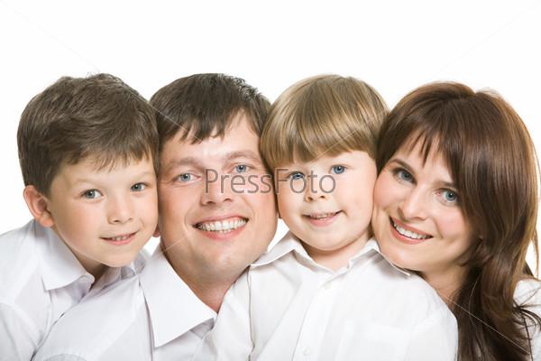 Счастливые родители и их двое сыновей улыбаясь смотрят в камеру