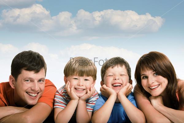 Семья со счастливыми лицами лежит в ряд на фоне белых облаков