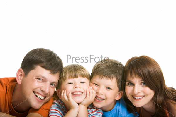 Дружная семья смотрит в камеру и улыбается на белом фоне