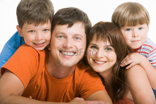 Фото семьи, которая радостно смеется глядя в камеру