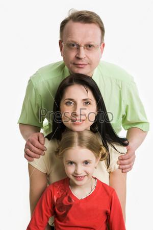 Семья из трех человек стоят друг над другом и смотрят в камеру и улыбаются
