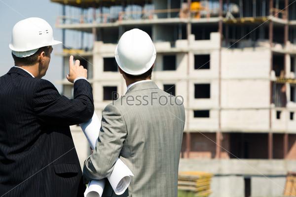 Успешный архитектор показывает партнеру на строящееся здание