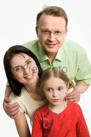 Мама, папа и дочь стоят все вместе на белом фоне