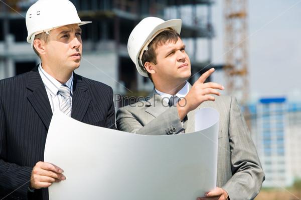 Два инженера держат чертеж и обсуждают проект строительства