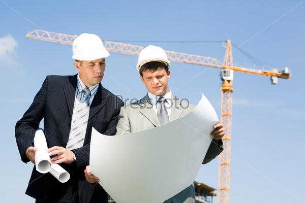 Два бригадира смотрят на чертеж проекта на фоне неба и подъемного крана
