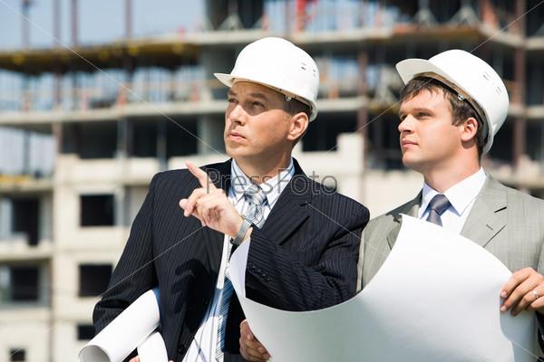 Фотография на тему Успешный архитектор объясняет и показывает бригадиру место строительства здания