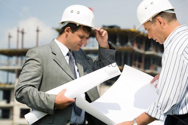 Двое строителей в касках рассматривают проект строительства дома