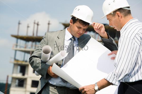 Двое мужчин в касках на строительной площадке изучают чертеж