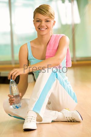 Девушка в спортивной форме сидит на полу в спортзале с бутылкой минеральной воды