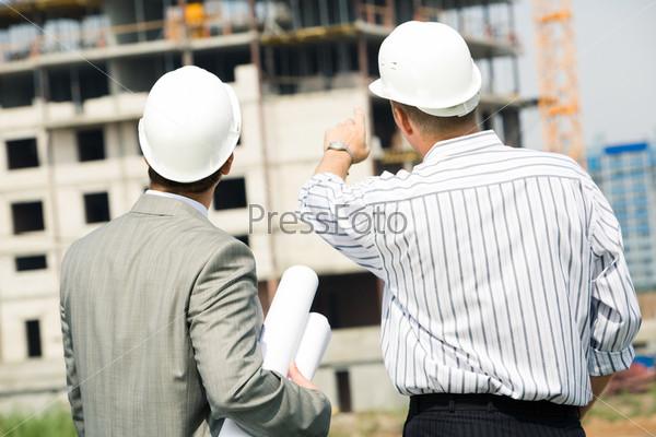 Два строителя в рубашках стоят спиной и показывают на строящееся здание