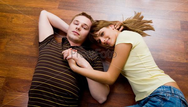 Романтичная молодая пара обнявшись лежит на полу и смотрит на камеру вверх