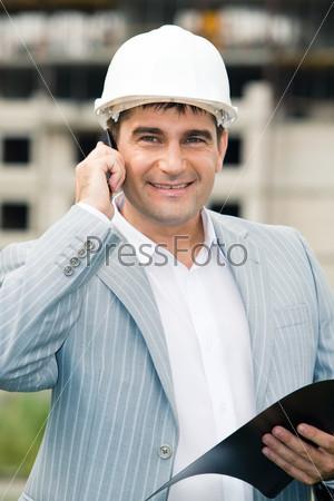 Довольный строитель держит в руках документы, разговаривает по телефону и улыбается