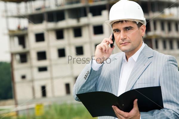 Бригадир разговаривает на стройке по сотовому телефону с начальником, в руках держит документы