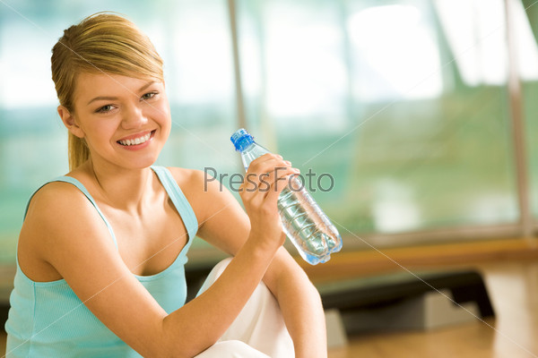 Привлекательная молодая девушка в голубой майке держит бутылку с водой в руке и улыбается