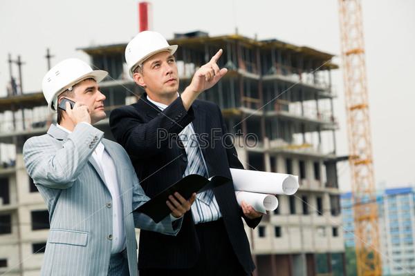 Начальник разговаривает по сотовому телефону на строительной площадке, рядом сторит прораб и показывает на здание