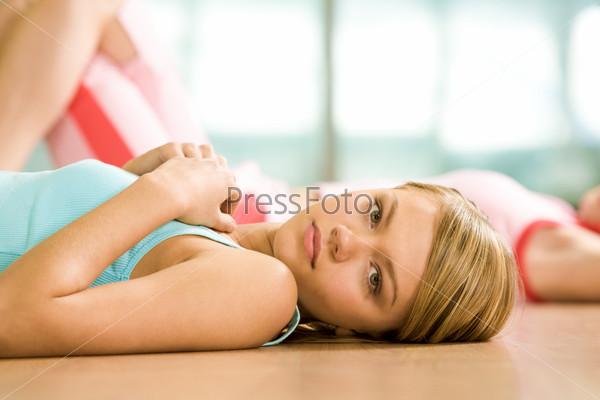 Красивая девушка лежит на спине в спортивном зале на полу и смотрит в камеру