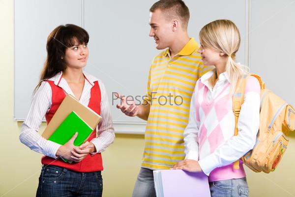 Две студентки и их одногруппних стоят в аудитории возле белой доски и общаются