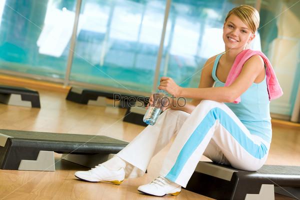 Спортсменка отдыхает с бутылкой воды и полотенцем на плече, смотрит в камеру и улыбается