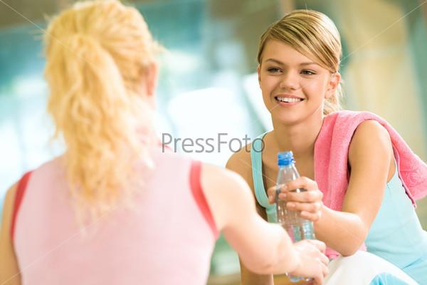 Добрая девушка угощает свою подругу водой в спортзале после тяжелой тренировки