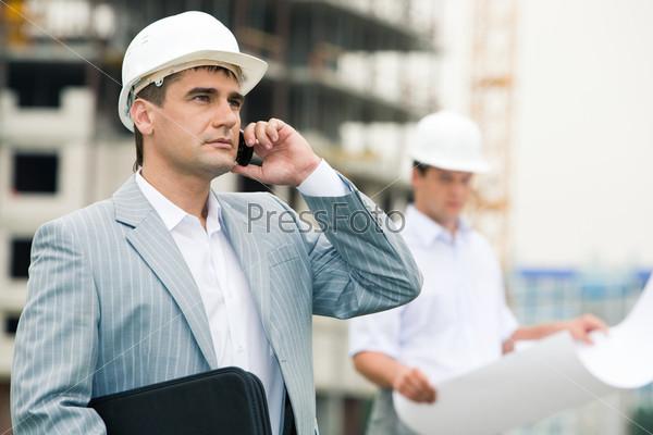 Современный успешный бизнесмен говорит по мобильному телефону на строительной площадке с  поставщиками материалов