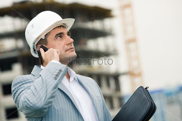 Деловой мужчина на стройке осматривает возводимое здание и разговаривает по телефону
