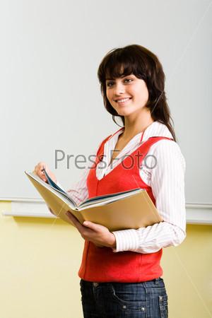 Девушка уверенно выступает с докладом у доски держа в руках папку с учебными материалами