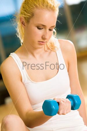 Серъезная блондинка в белой майке держит в руках гантелю в спортивном зале