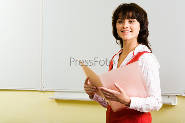 Студентка стоит у доски с розовой папкой и улыбается