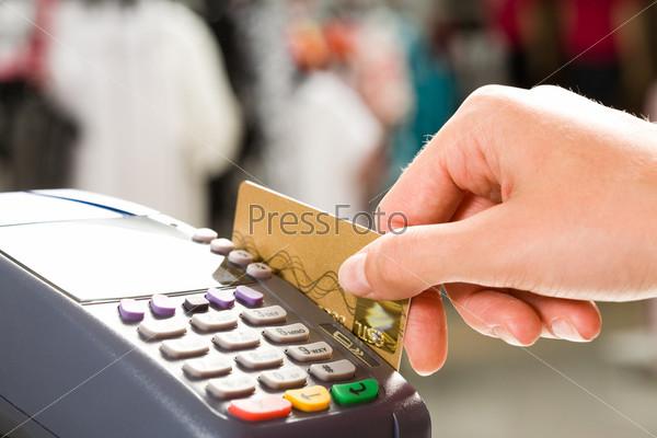 Крупный план руки держащей кредитную карту вставленную в терминал