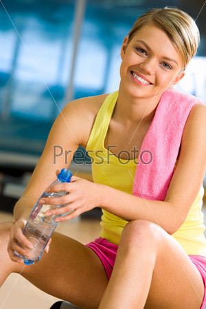 Радостная девушка сидит в спортивном зале держа в руках бутылку с водой