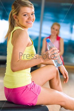 Красивая блондинка вытянув ногу сидит в гимнастическом зале держа в руке бутылку с минеральной водой