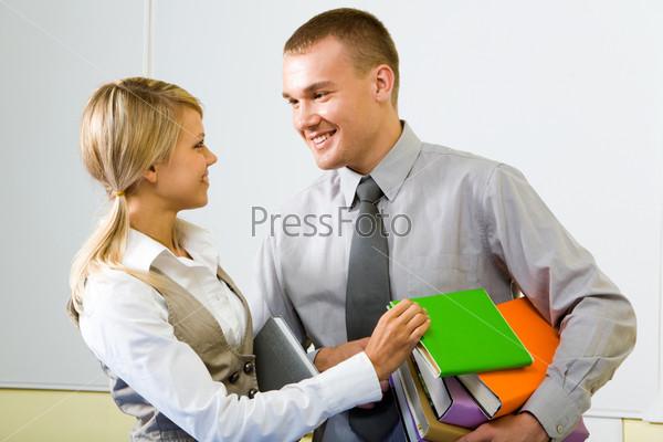 Студент стоит рядом с однокурсницей держа в руках стопку папок и учебников и улыбается ей