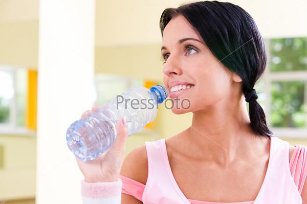 Крупный план девушки в розовой майке, которая держит в руках бутылку с водой и улыбается