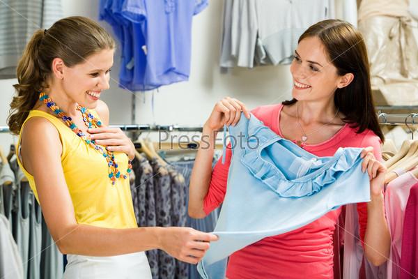 Две девушки рассматривают голубую блузку в магазине