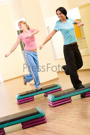 Две девушки занимаются аэробикой стоя на одной ноге и глядя в сторону в спортивном зале