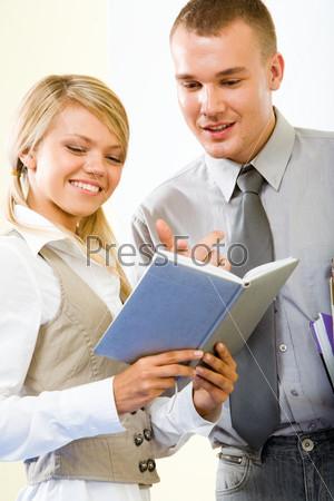 Молодой человек смотрит расписание занятий в блокноте у сокурсницы, которая держит его в руках