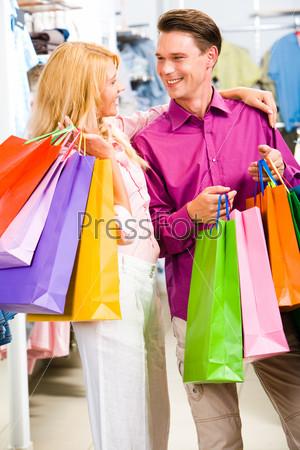 Молодая семейная пара стоит в центре магазина и смотрит друг на друга с улыбкой держа в руках яркие пакеты с покупками