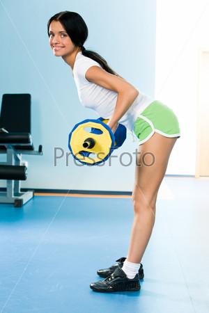 Энергичная девушка стоя на полу поднимает штангу и улыбается