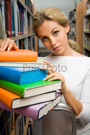 Очаровательная девушка положила руку на стопку ярких книг в библиотеке