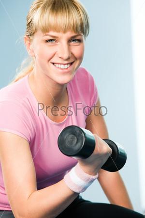 Радостная девушка крепко держит гантелю в руке и улыбается