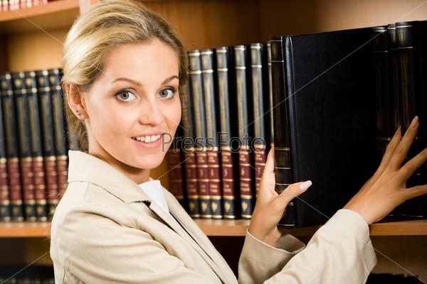 Успешная молодая женщина стоит рядом с полкой с книгами и улыбается