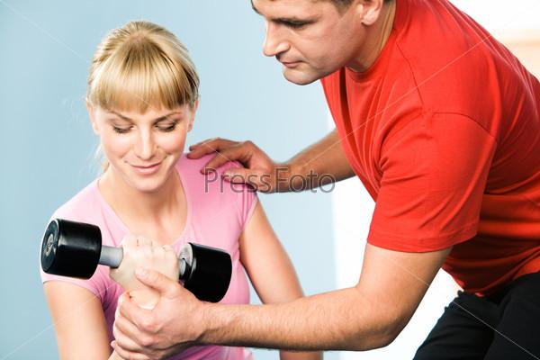 Инструктор держит за руку девушку, которая выполняет упражнение с гантелями в спортзале